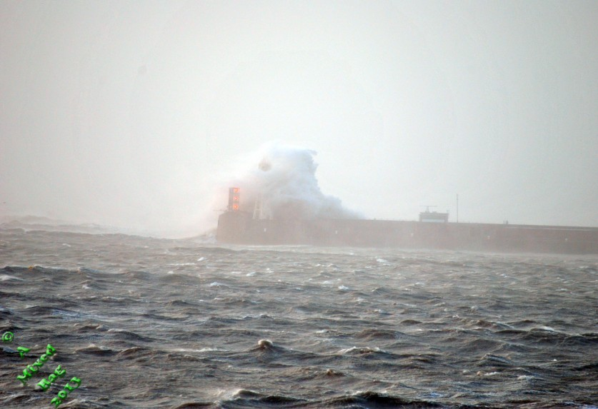 Waves engulfing a lighthouse