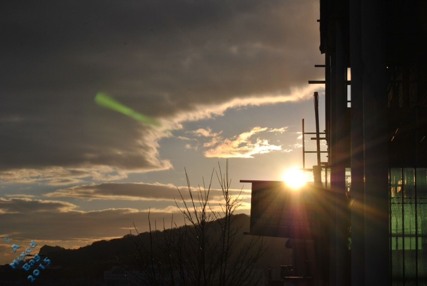 The sun setting behind buildings